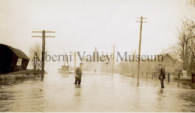 "From the AV Museum entry: ""circa 1935-01-00 DescriptionA northward view of the 1935 winter flooding on River Road shows two men wading across the road as the Somass River (at left) floods its banks. The building at left (with a sign on it) appears to be either sagging or toppling from the flood damage. A fishboat further up River Road is tied to a telephone pole. Hydro poles are at right of image, while telecommunications poles are at left."""