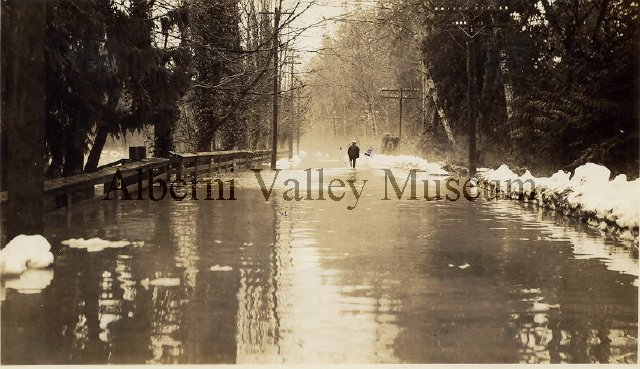 "From the AV Museum description: ""A man is seen in the distance walking away from the camera down River Road. A fence is at left, with snow piles at right. Telephone power lines are on either side of the road. These are the effects of the 1935 winter flooding of the Somass River."""