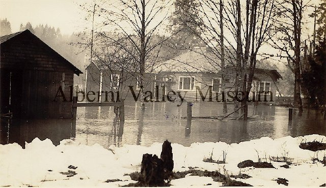 "from the AV Museum Description: ""An intact house stands in a flooded yard due to the 1935 winter flooding of the Somass River. A shed is visible alongside the fence at left of image. Some snow is on the ground. A building (possibly) is faintly visible across the river in the background. Stamped on back: ""[...] CLEGG'S STUDIO / PHOTOGRAPHER / PORT ALBERNI, B.C. / Local Views of the District. [...]"""""